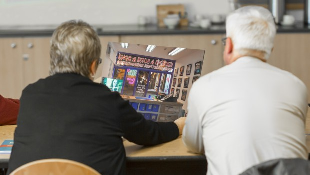 Two people are shot from behind, sitting next to one another. In between them they are holding and considering a poster of the image from within a shop, looking out through the shopfront.