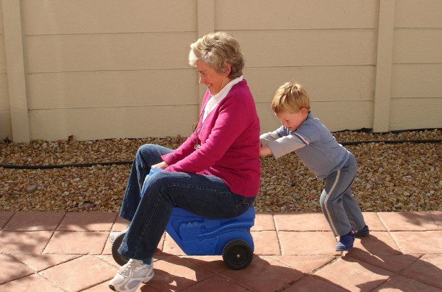 Child pushing grandmother on plastic tricycle (credit: Catherine Scott-Matti/CC BY-SA 2.0)