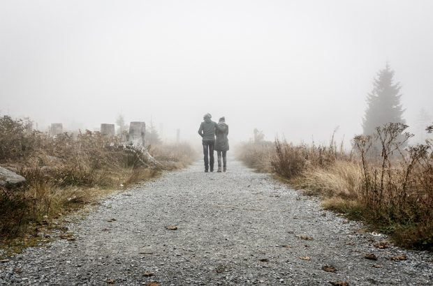 Two people walking on a road through the mist (Sebastian Pichler / CC0)
